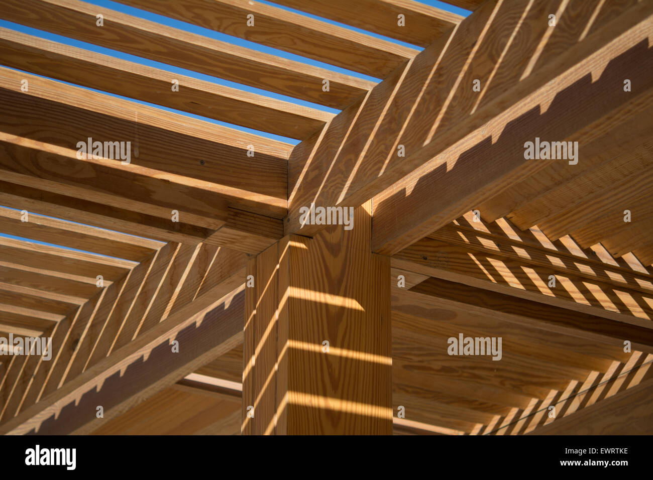 Stock Photo   Wooden Slotted Roof Support Pillar With Sunlight Shining  Through The Slats Onto The Wood Below
