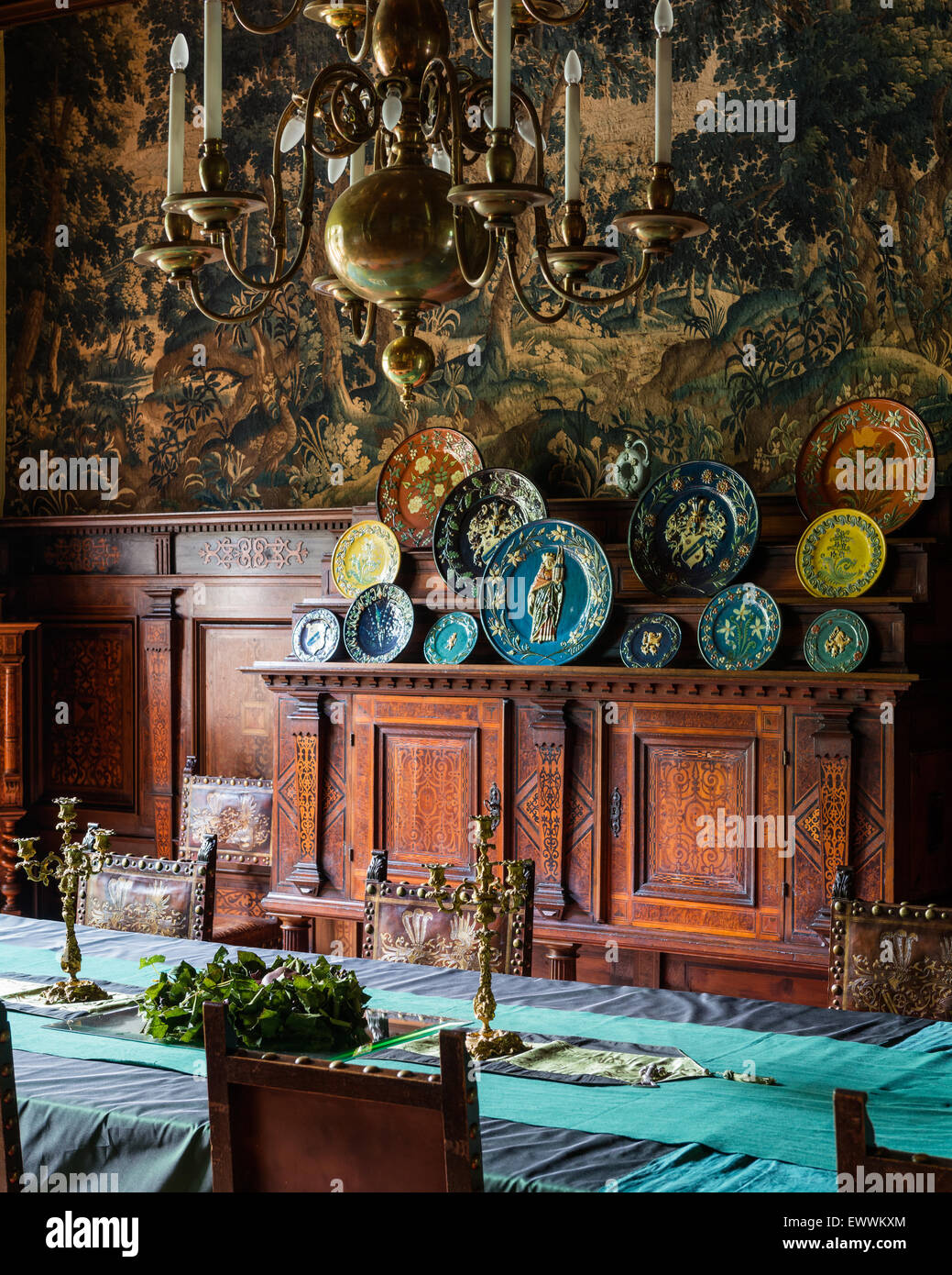 Ornate wooden cabinet with decorative plates in dining room with ornate wooden cabinet with decorative plates in dining room with brass chandelier arubaitofo Images