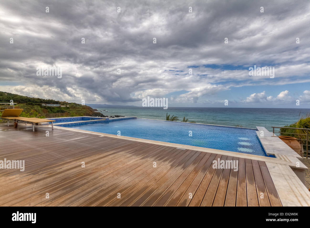 Dramatic View Of Swimming Pool And Deck Overlooking Sea On A Cloudy Stock Photo Royalty Free