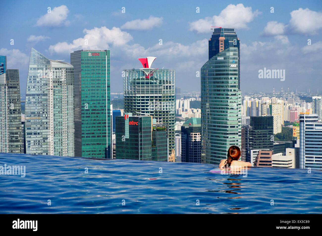 Woman at the mbs infinity pool and enjoying the singapore skyline stock photo royalty free - Singapur skyline pool ...