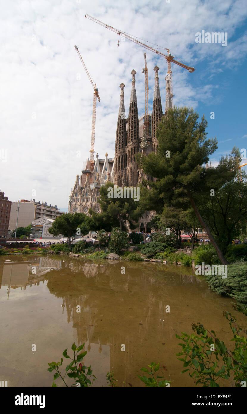 looking across the lake in placa de gaudi gardens towards la sagrada familia