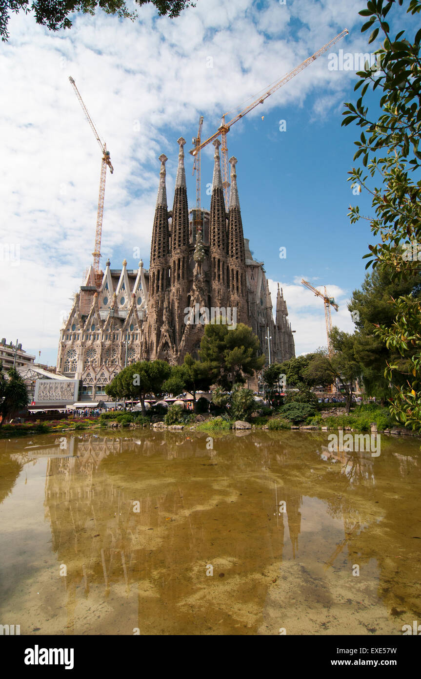 looking across placa de gaudi gardens lake towards la sagrada familia