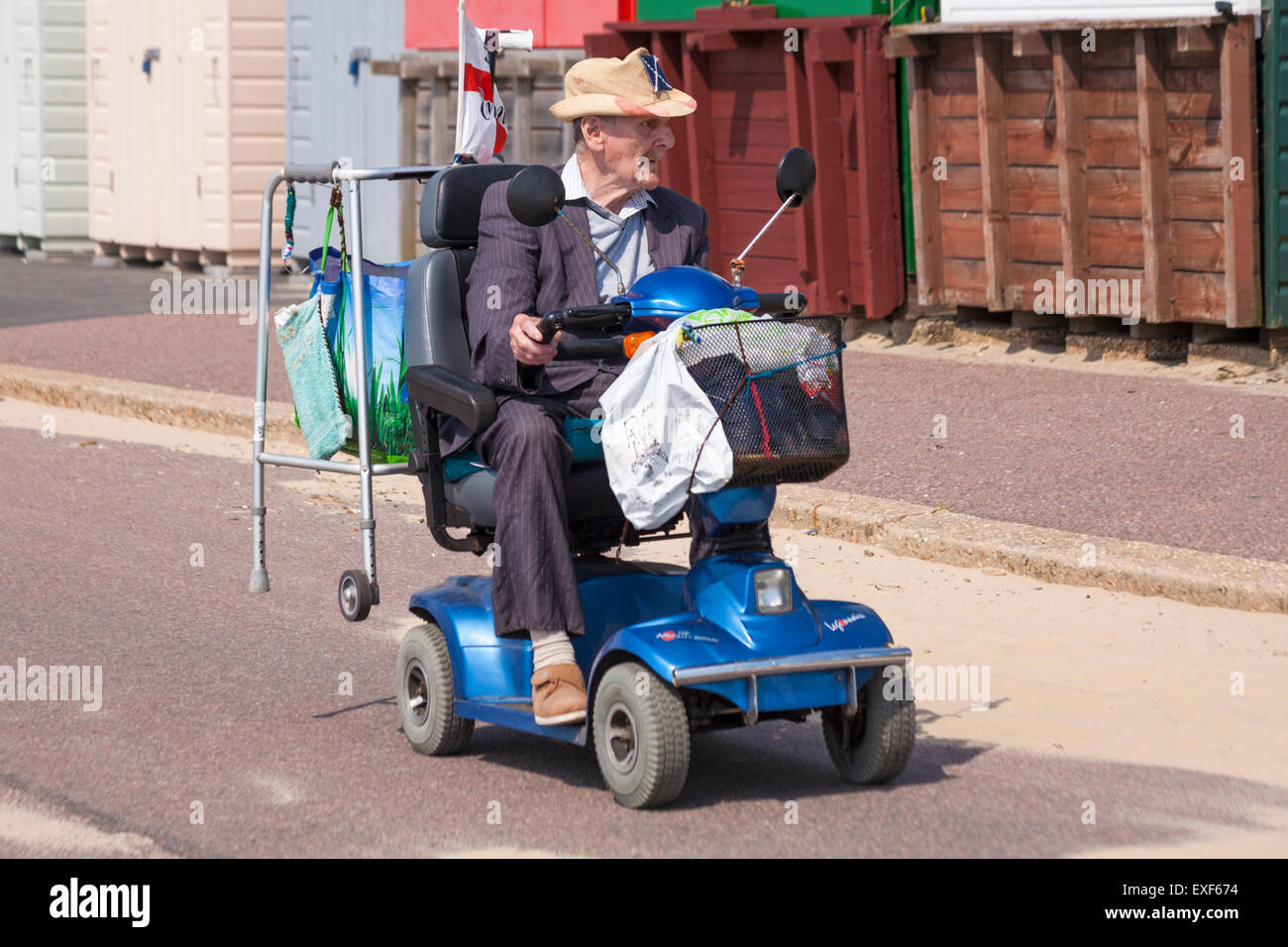 Elderly man on mobility scooter driving past row of beach for Motorized cart for seniors