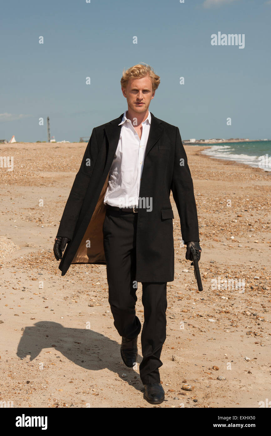 man in a long black coat holding a gun and walking on the beach ...