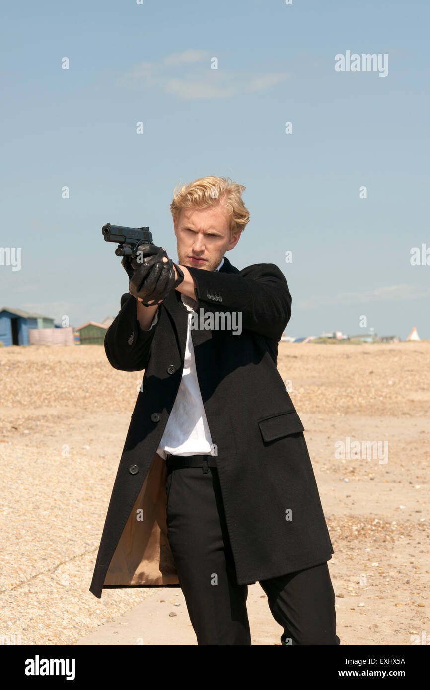 Man In A Long Black Coat Holding A Handgun And Aiming To Shoot Or