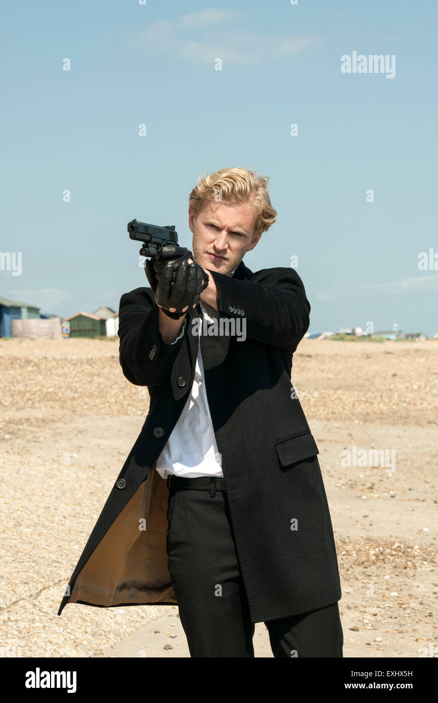 man in a long black coat holding a handgun and aiming to shoot or ...