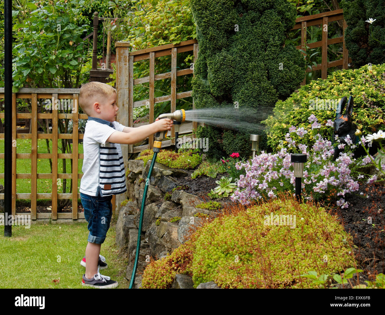 Toddler with hose pipe watering garden plants stock photo for Watering vegetable garden