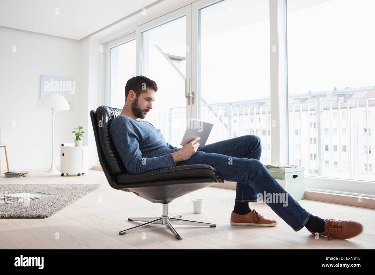 Man Living Room Young Man Sitting On Leather Chair In His Living Room Using