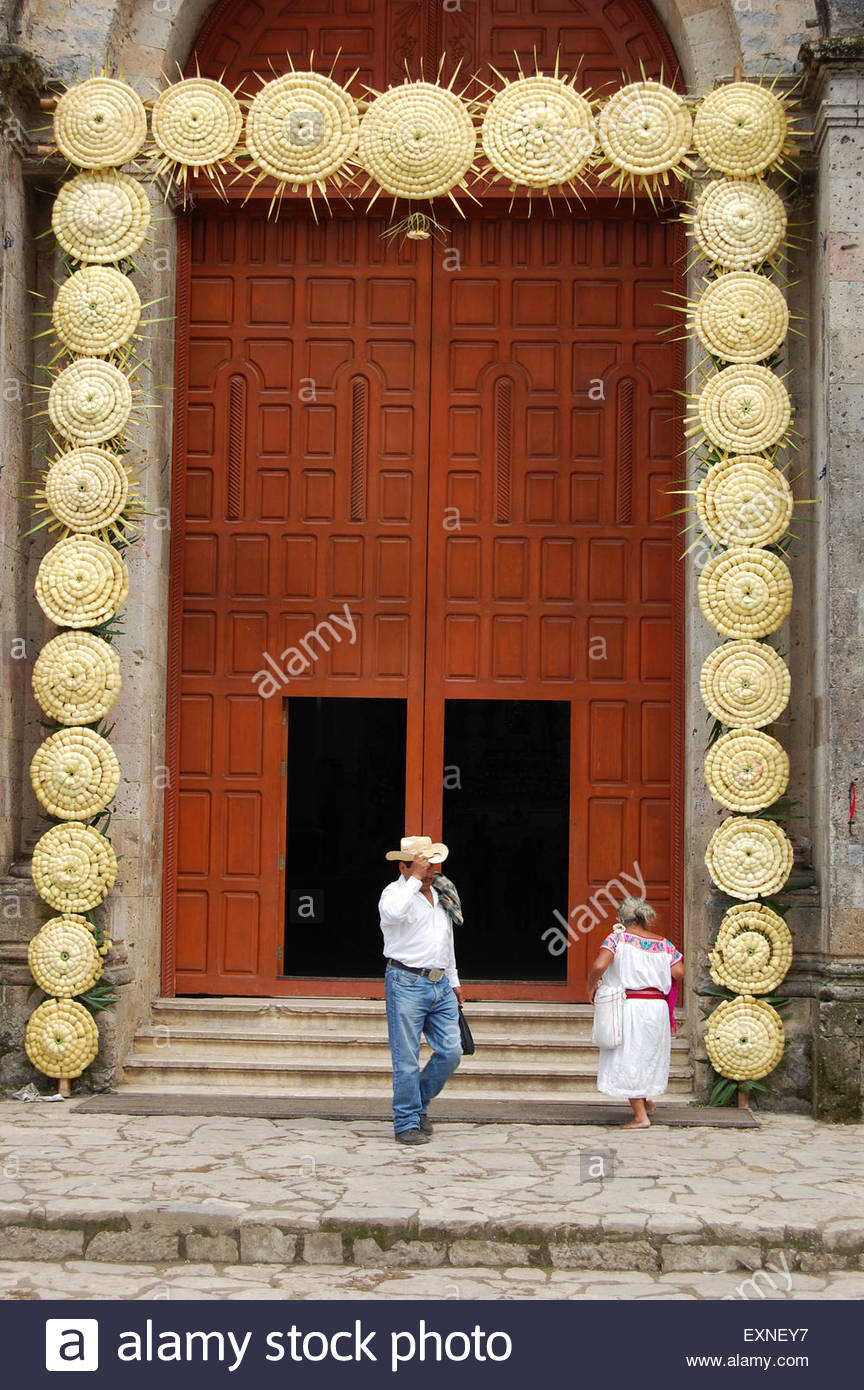 Street shot Mexico large church wooden door with cowboy in hat leaving and indigenous Mexican woman entering church & Street shot Mexico large church wooden door with cowboy in hat ...