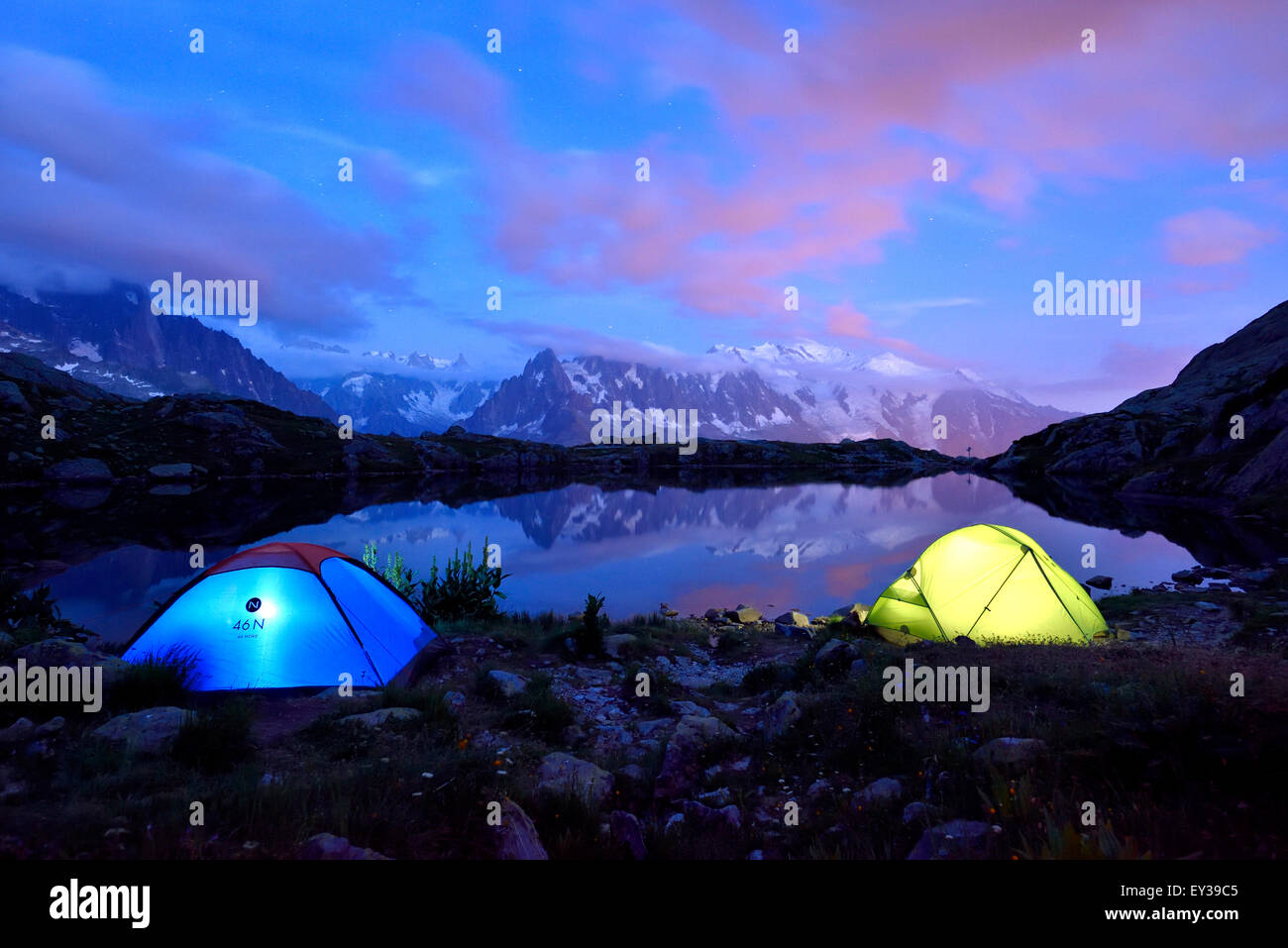 Mont Blanc massif at night reflected in Lac de Chésserys two lighted tents at the front Chamonix France & Mont Blanc massif at night reflected in Lac de Chésserys two ...