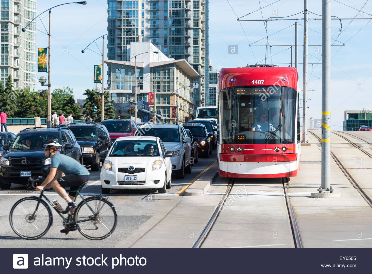 Cyclist Passing By A Traffic Junction As Cars And A Tram Wait For