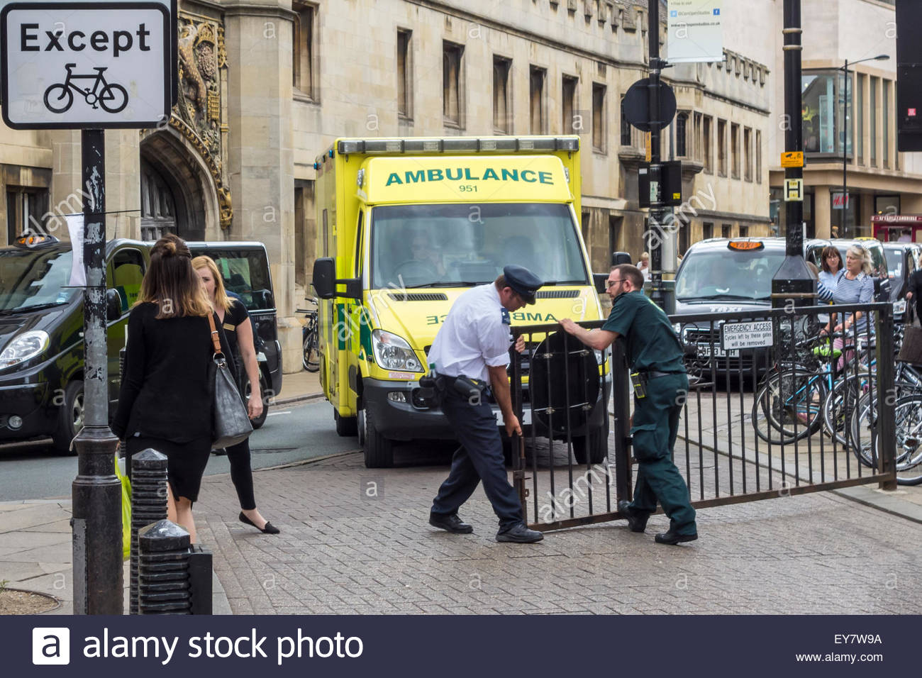 Ambulance staff and a security guard opening an access