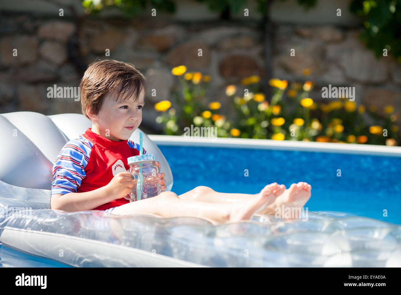 Little Boy In A Big Swimming Pool Drinking Juice In A Hot