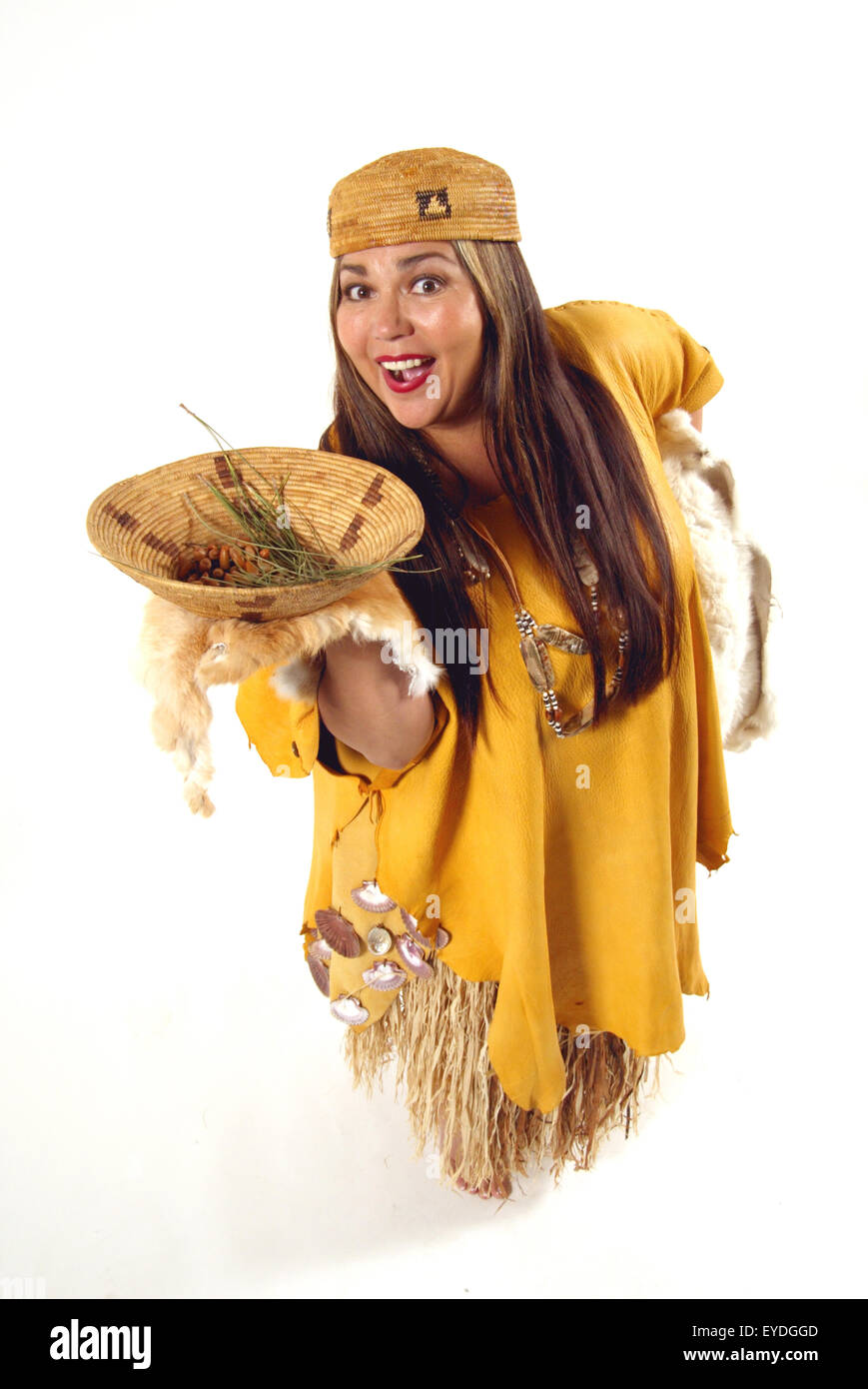 An Acjachemen or Juaneno Native American woman in traditional costume displays a basket of local produce in a basket