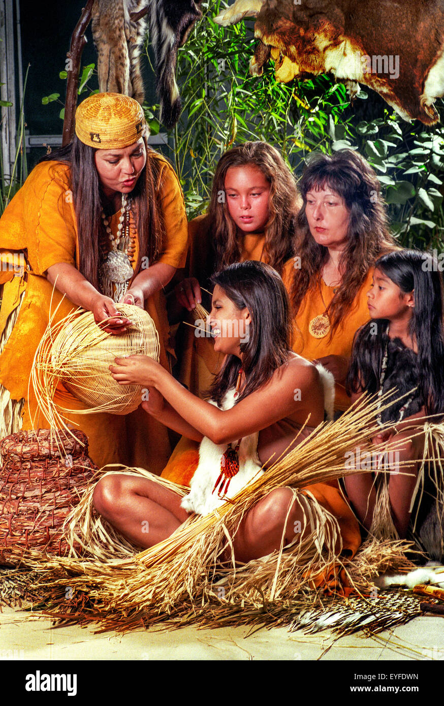 Wearing historical costumes, members of the California tribe of Acjahemen or Juaneno Indians in San Juan Capistrano, CA, reenact an ancient teaching scene where older members explain tribal lore to younger ones. This scene involves basket weaving.