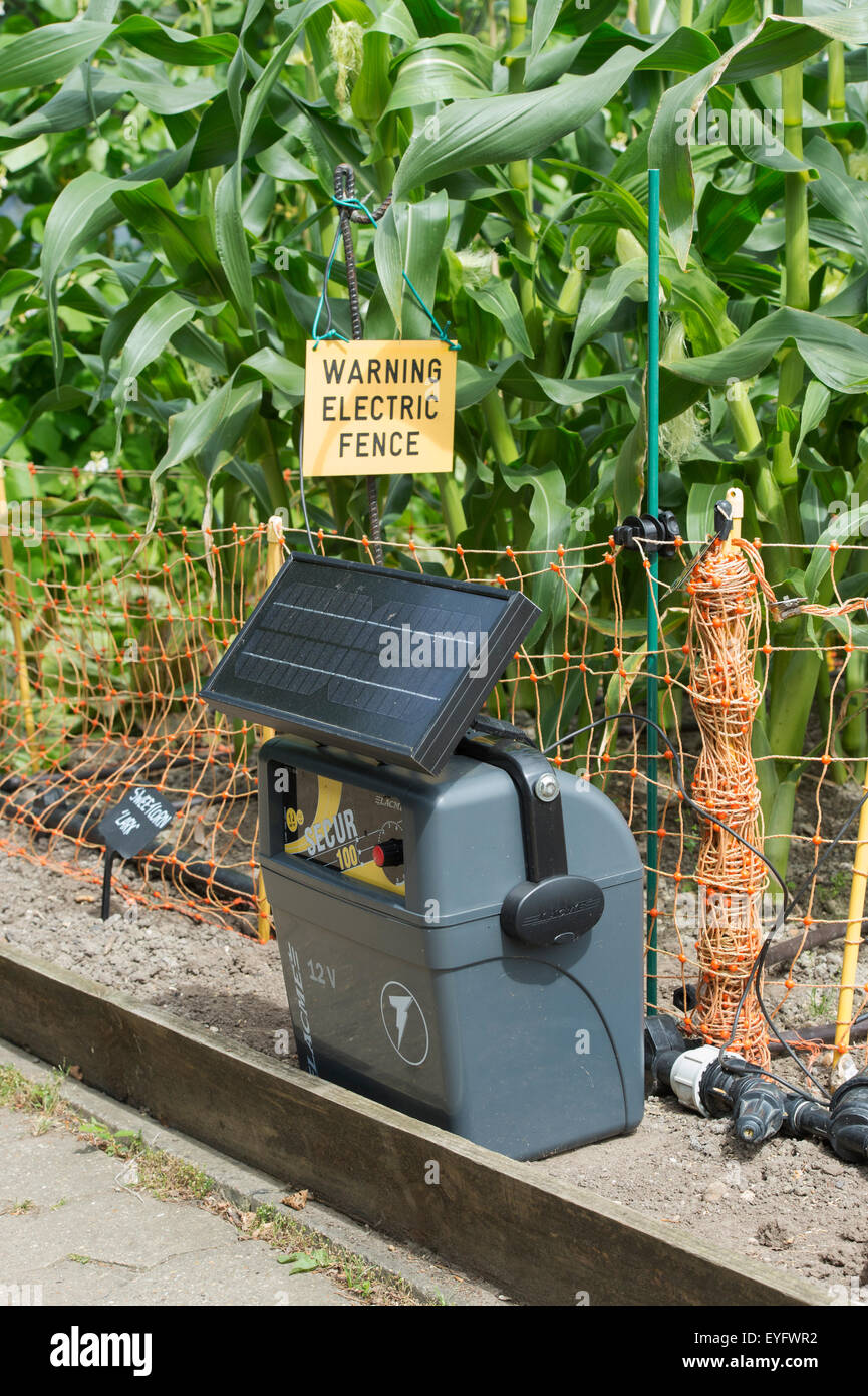 Portable Solar Power Battery Unit And Electric Fence Around A Crop