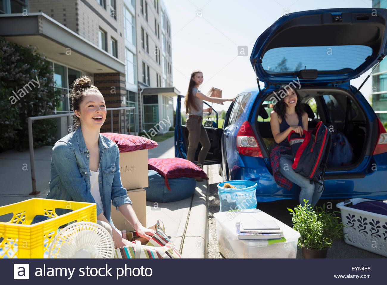 college students unloading car moving into college dorm stock college students unloading car moving into college dorm
