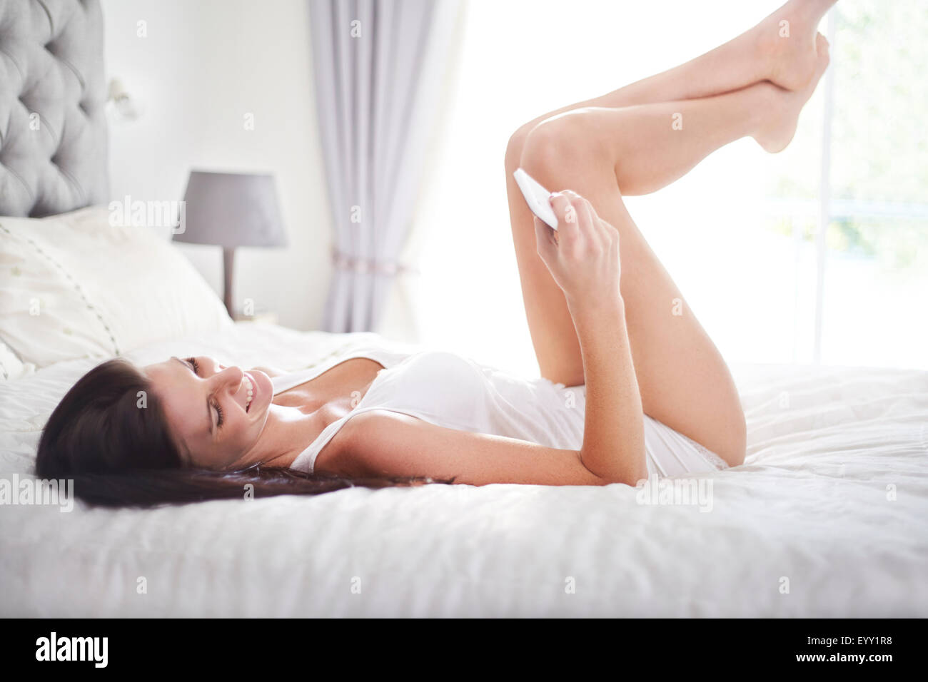woman laying on bed texting with cell phone stock photo, royalty