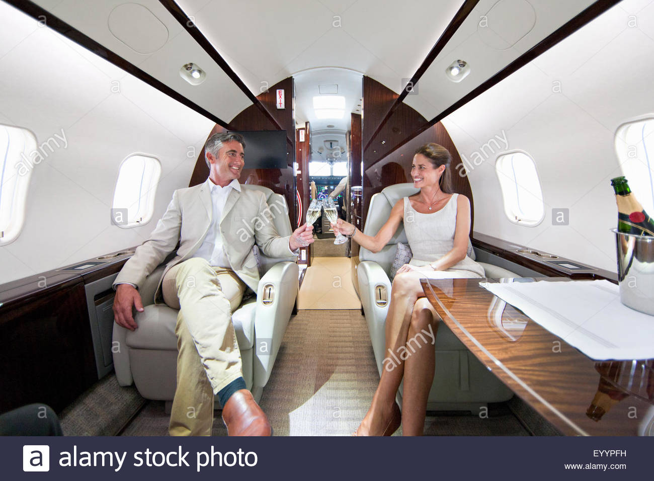 Private Jets For Rent >> Smiling couple making a toast with champagne in private ...