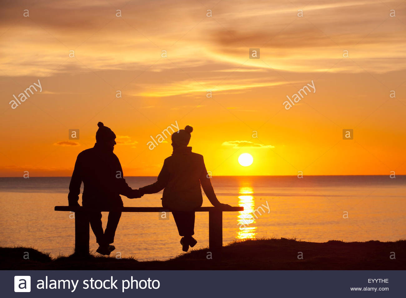Silhouette of couple, sitting on bench, holding hands, against ... for Couple Holding Hands Silhouette Sunset  56bof