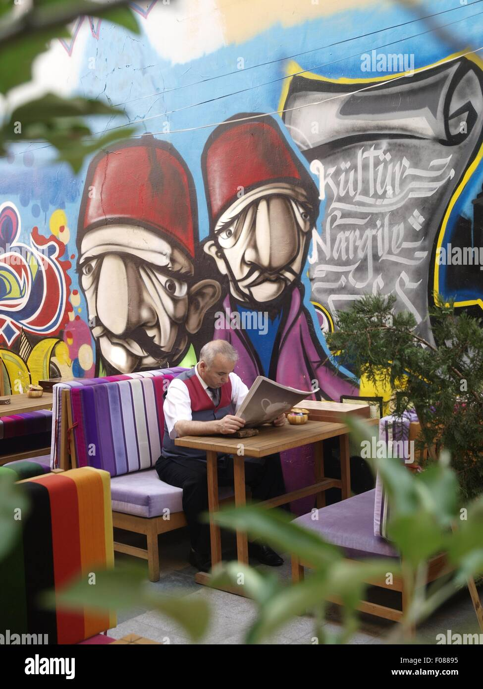 Graffiti wall reading - People Sitting Beside Graffiti Wall At Street Cafe And Reading Newspaper Istanbul Turkey