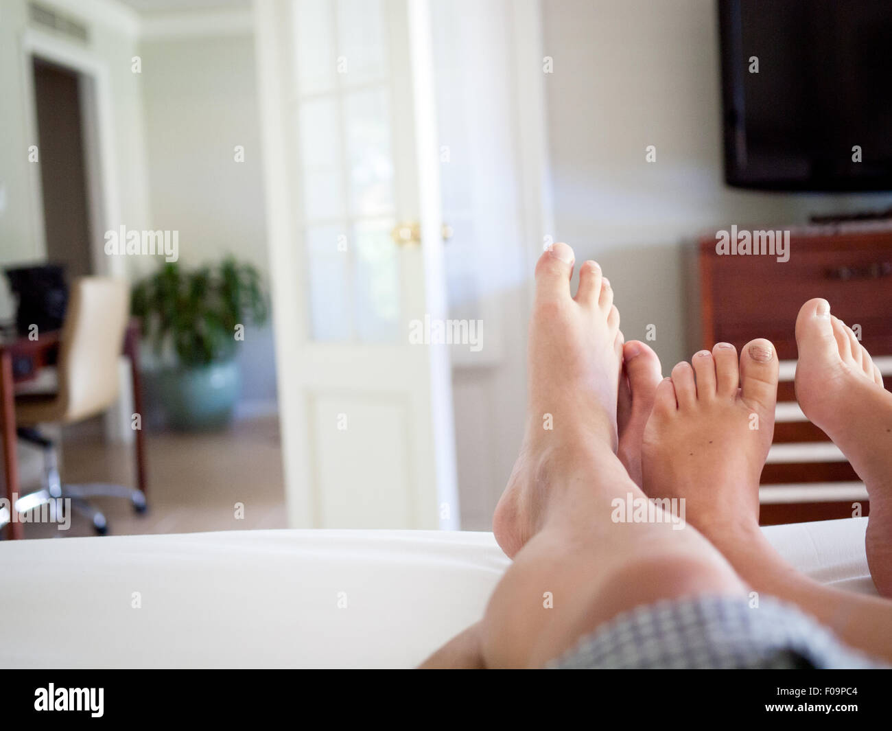 the feet of a man and woman in bed in a hotel room suite at the
