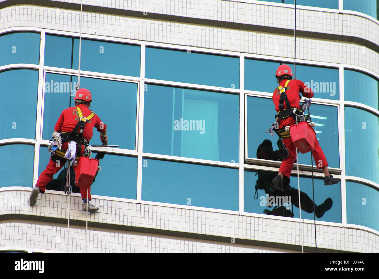 risky life window cleaners in action hanging on a chair rop decent system