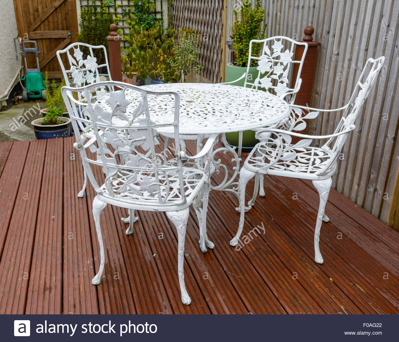 Stock Photo   White Cast Iron Garden Table And Chairs In A Back Garden