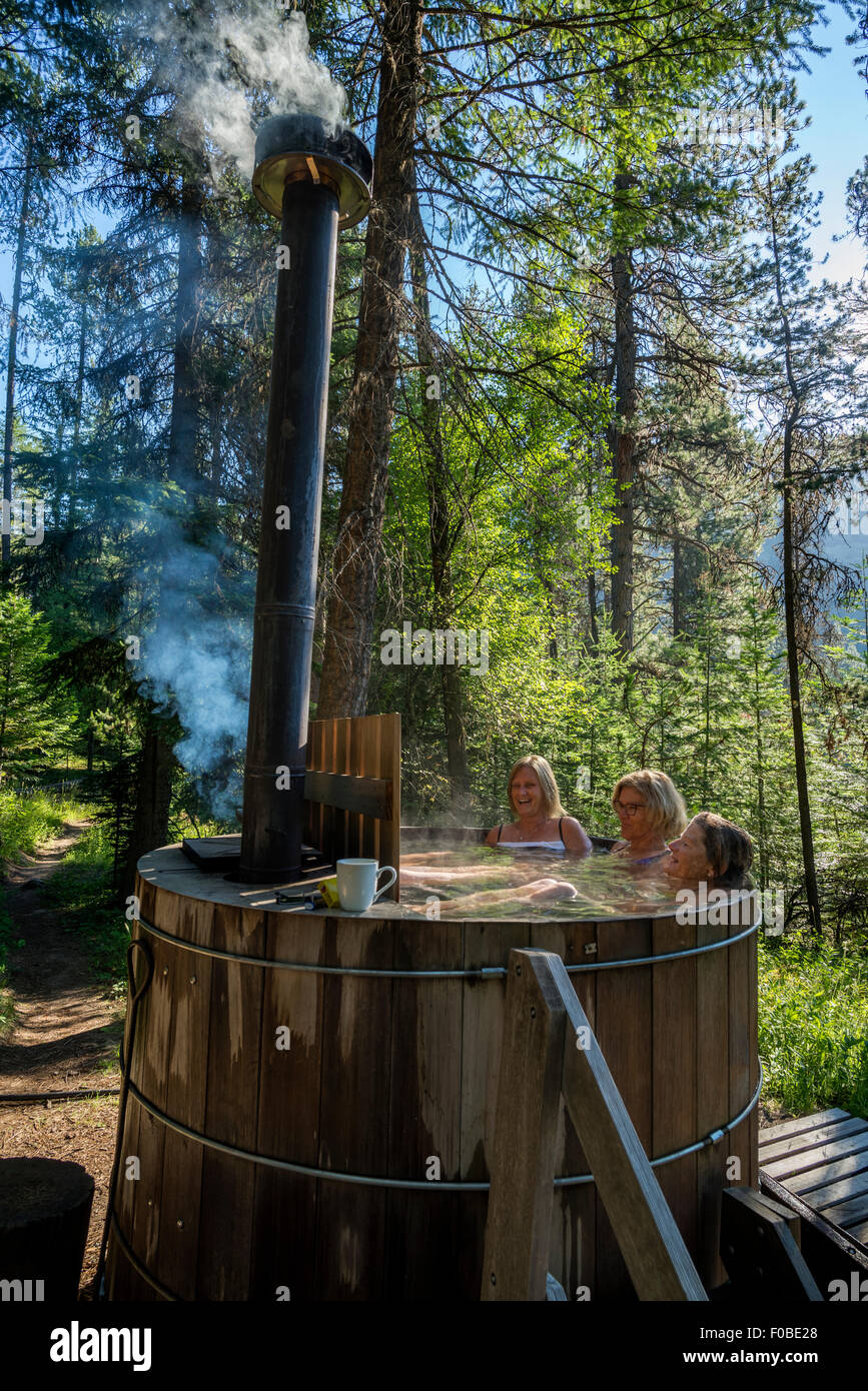 stock photo women soaking in a woodfired hot tub at the minam river lodge oregon