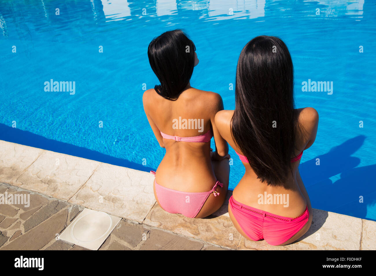 Back view portrait of a two young women sitting near swim - Where is my nearest swimming pool ...
