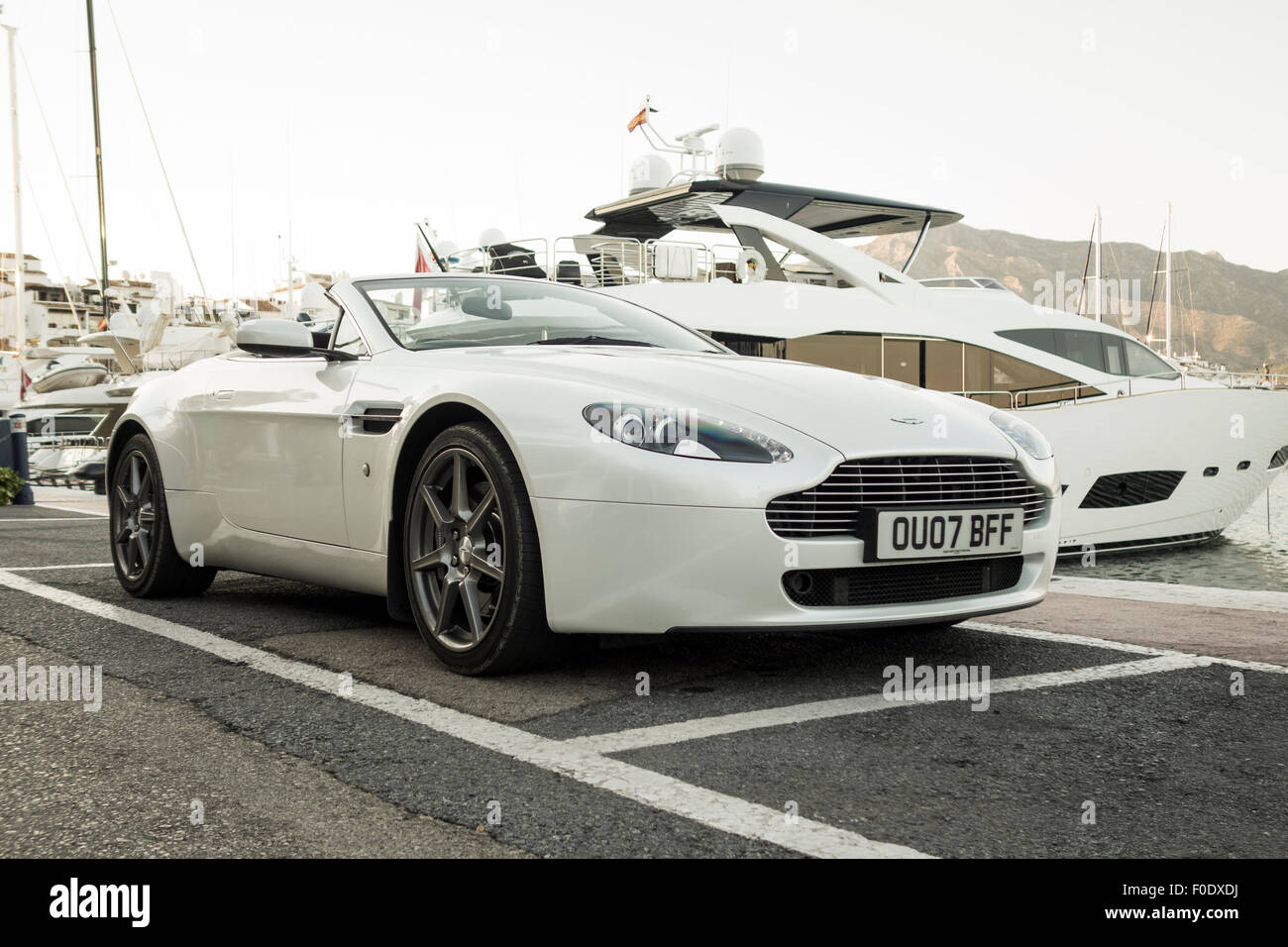 aston martin vantage v8 sports car parked in front of luxury yacht stock photo royalty free. Black Bedroom Furniture Sets. Home Design Ideas