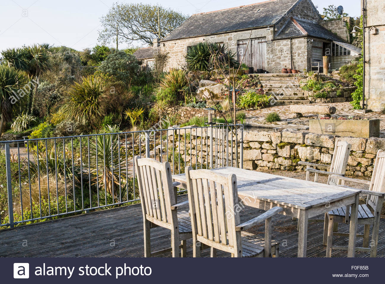 elevated decking with metal boundary and wooden garden furniture chygurno lamorna cornwall uk
