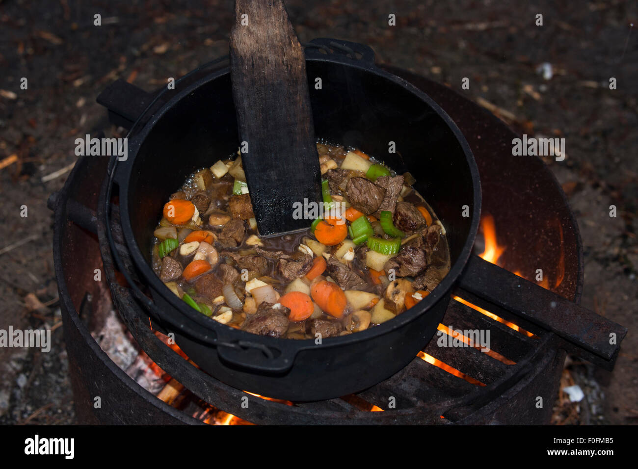 Beef stew cooking in a cast iron dutch oven over an open for How to cook in a dutch oven over a campfire
