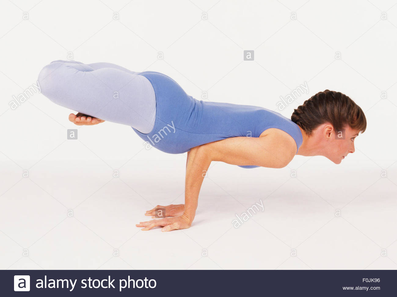 Stock Photo   Yoga Woman Doing The Peacock Mayurasana In Lotus Position  Hands Flat On Floor Supporting Body Elbows Pressing Into Midriff Head
