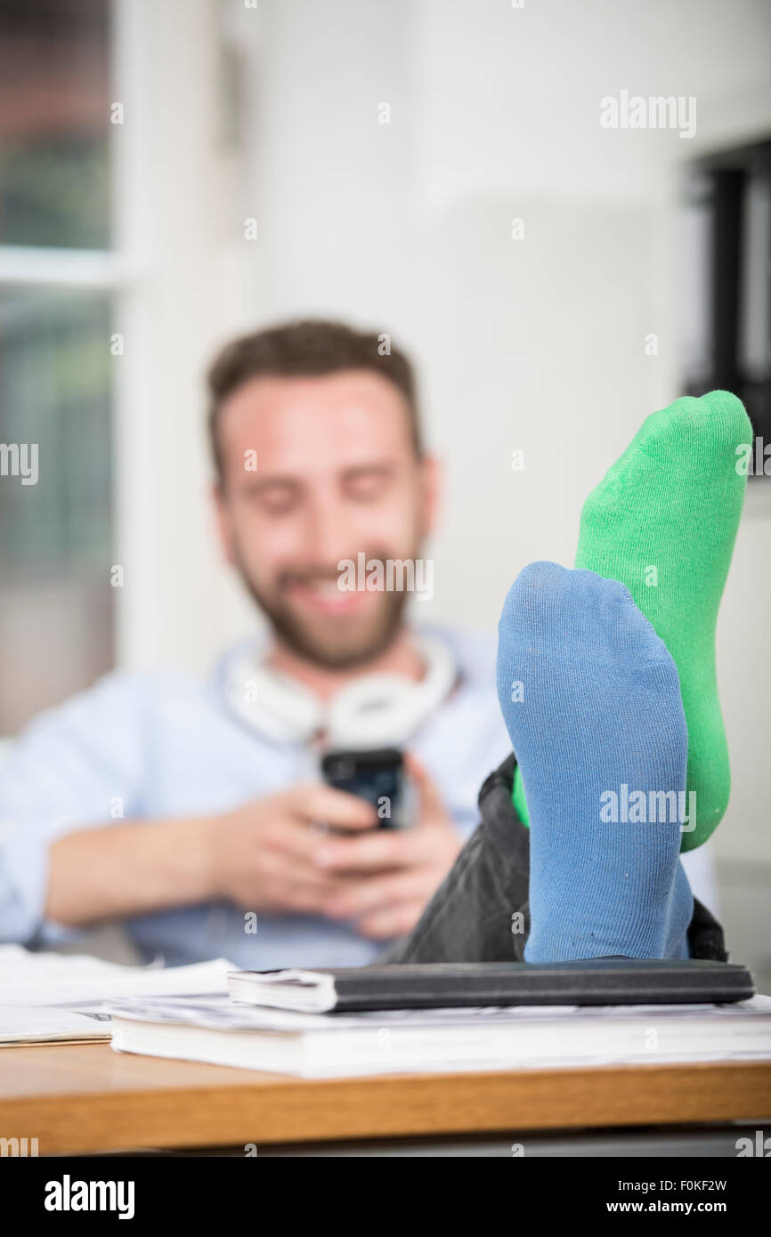 Young Man In Office With Feet On Desk Wearing Different
