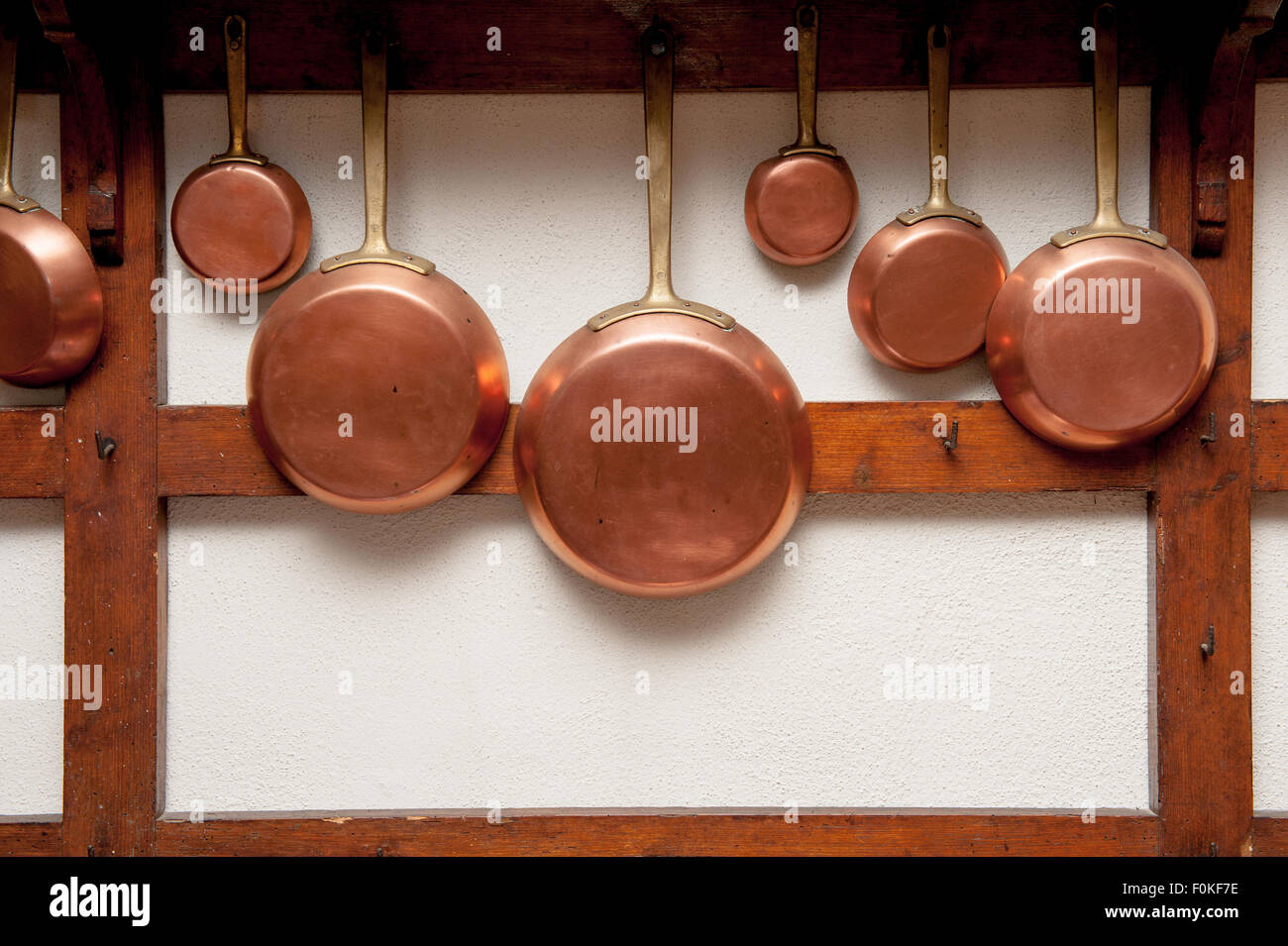 row of vintage copper pans different size hung on wooden shelf in kitchen vertical frame