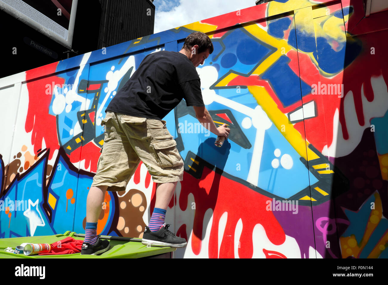 man spray painting graffiti on great eastern street hoarding in stock. Black Bedroom Furniture Sets. Home Design Ideas