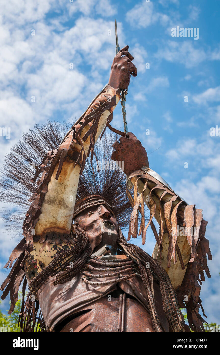 statue of native american man made of scrap metal by artist jay