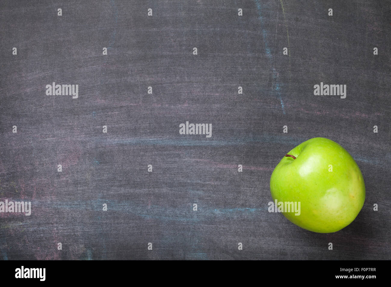 Green Apple On Blackboard Or Chalkboard Background Top View With Copy Space