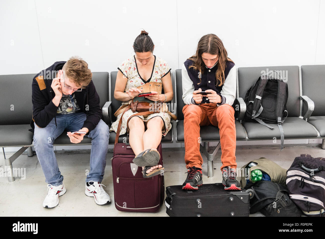 Passengers,travellers with carry on luggage checking their mobile ...