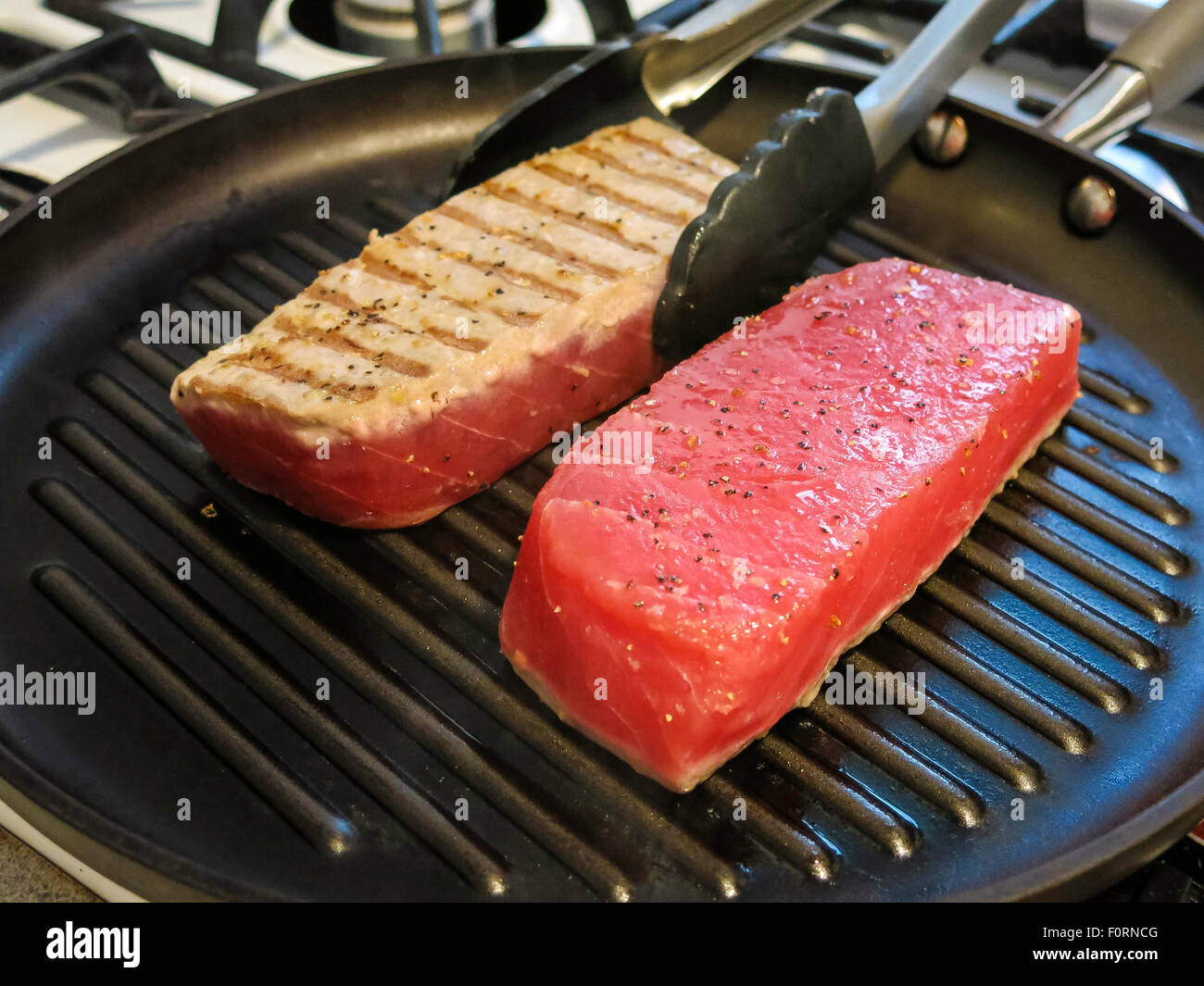 Sushi-Grade Raw Tuna Steaks Cooking on Stove Top Grill Pan Stock ...