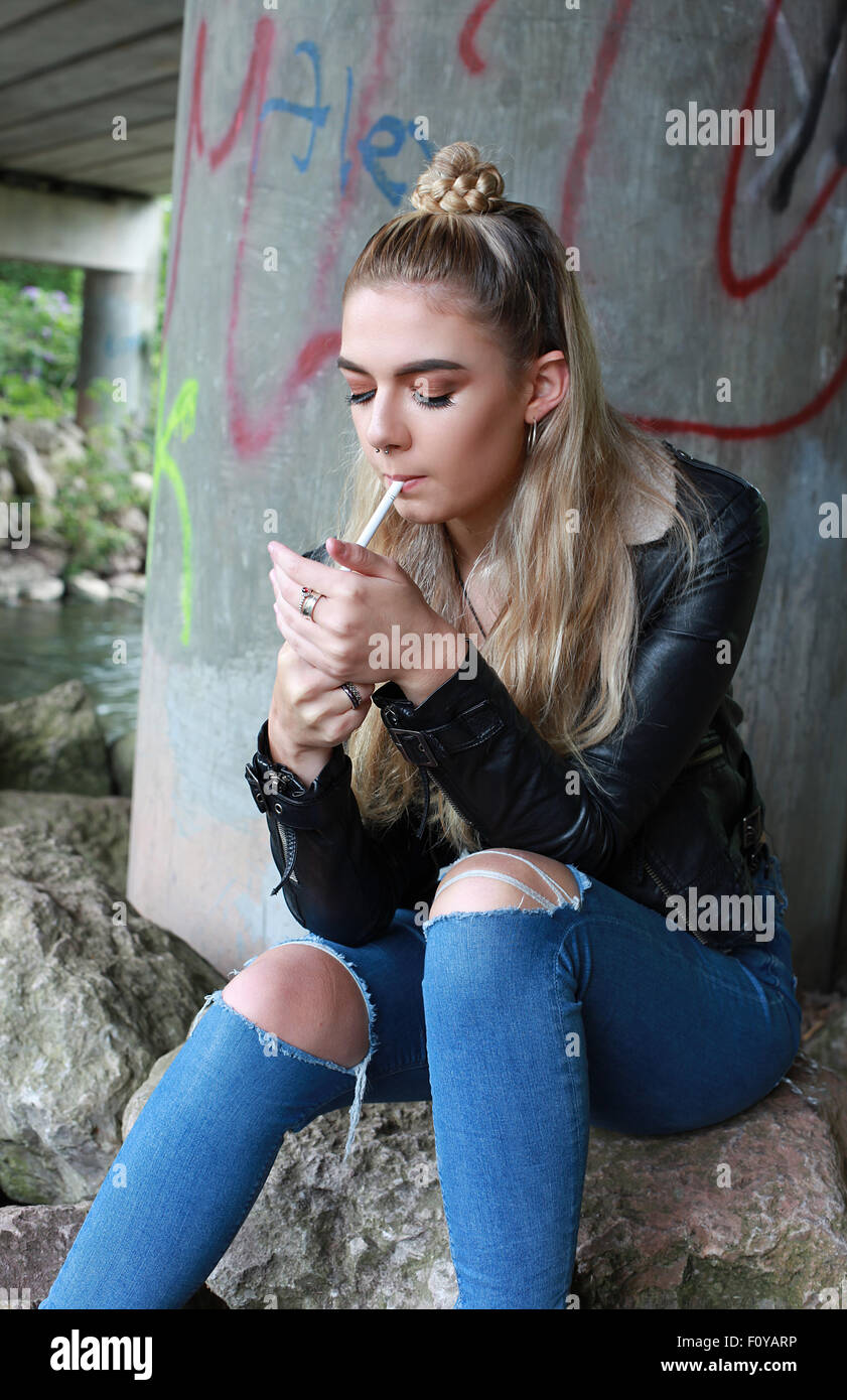 ... tough looking teenage girl with her nose pierced smoking a cigarette -  Stock Photo