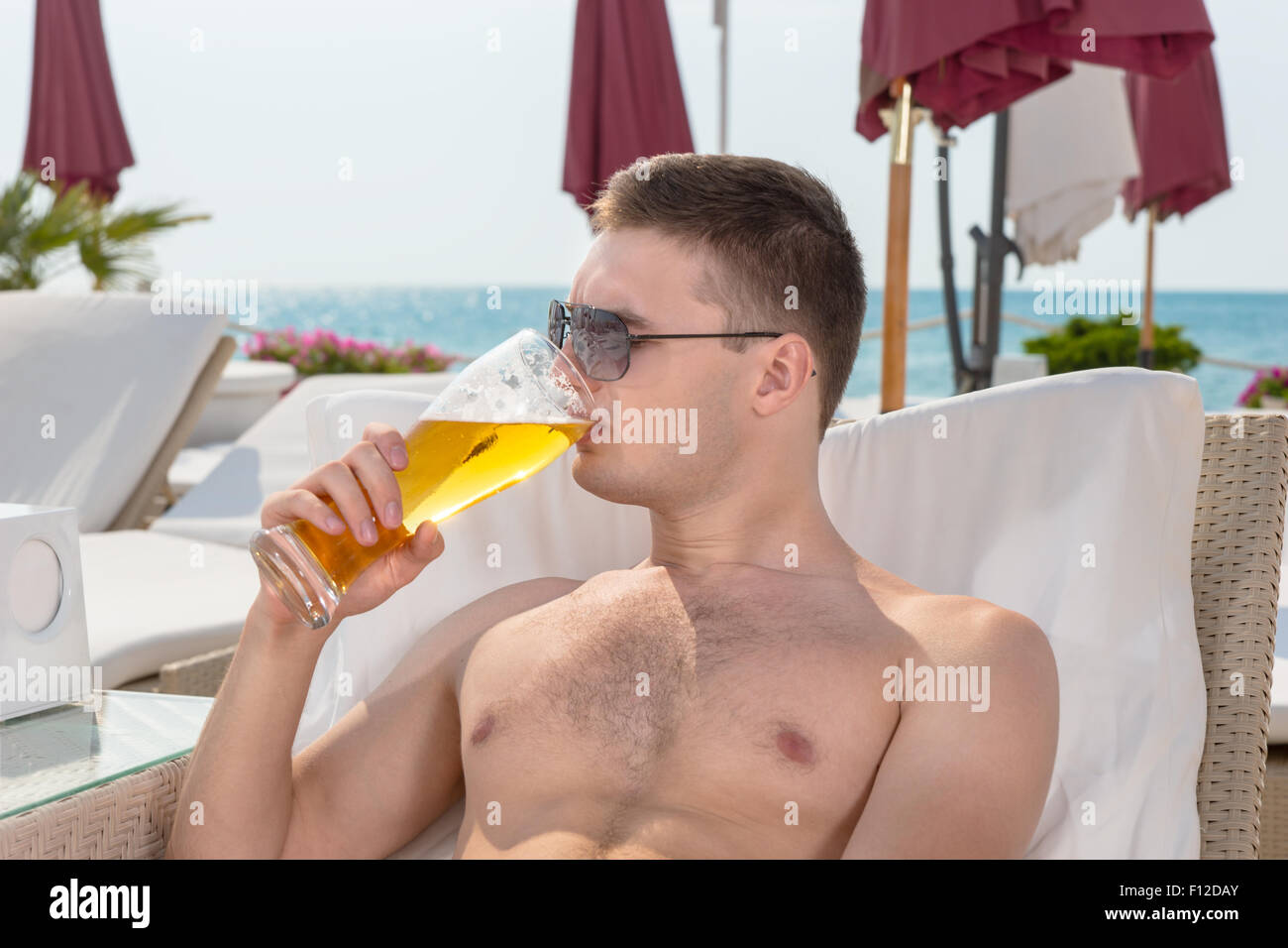 Stock Photo - Young man enjoying a cold beer as he relaxes on a recliner chair at a coastal resort with the ocean behind him  sc 1 st  Alamy & Young man enjoying a cold beer as he relaxes on a recliner chair ... islam-shia.org