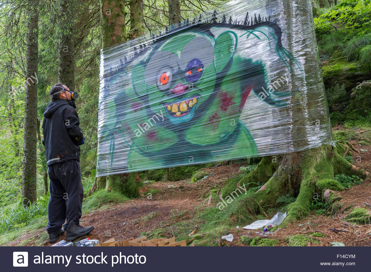 graffiti artist with spray can painting a troll onto