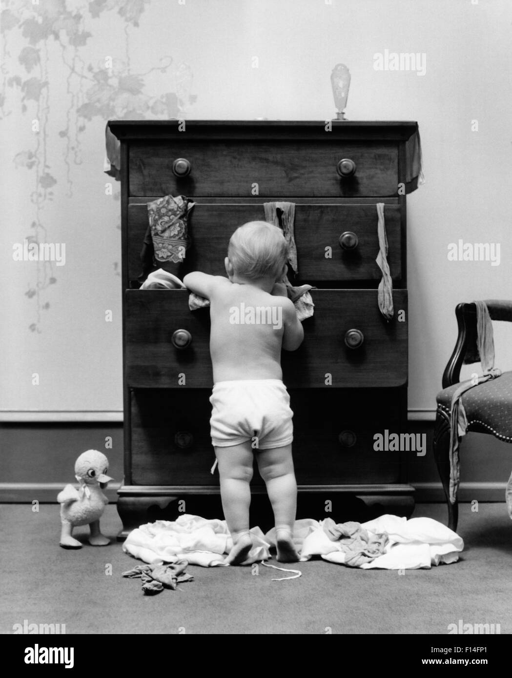 1940s TODDLER BABY PULLING CLOTHES OUT OF BUREAU DRAWERS MAKING A