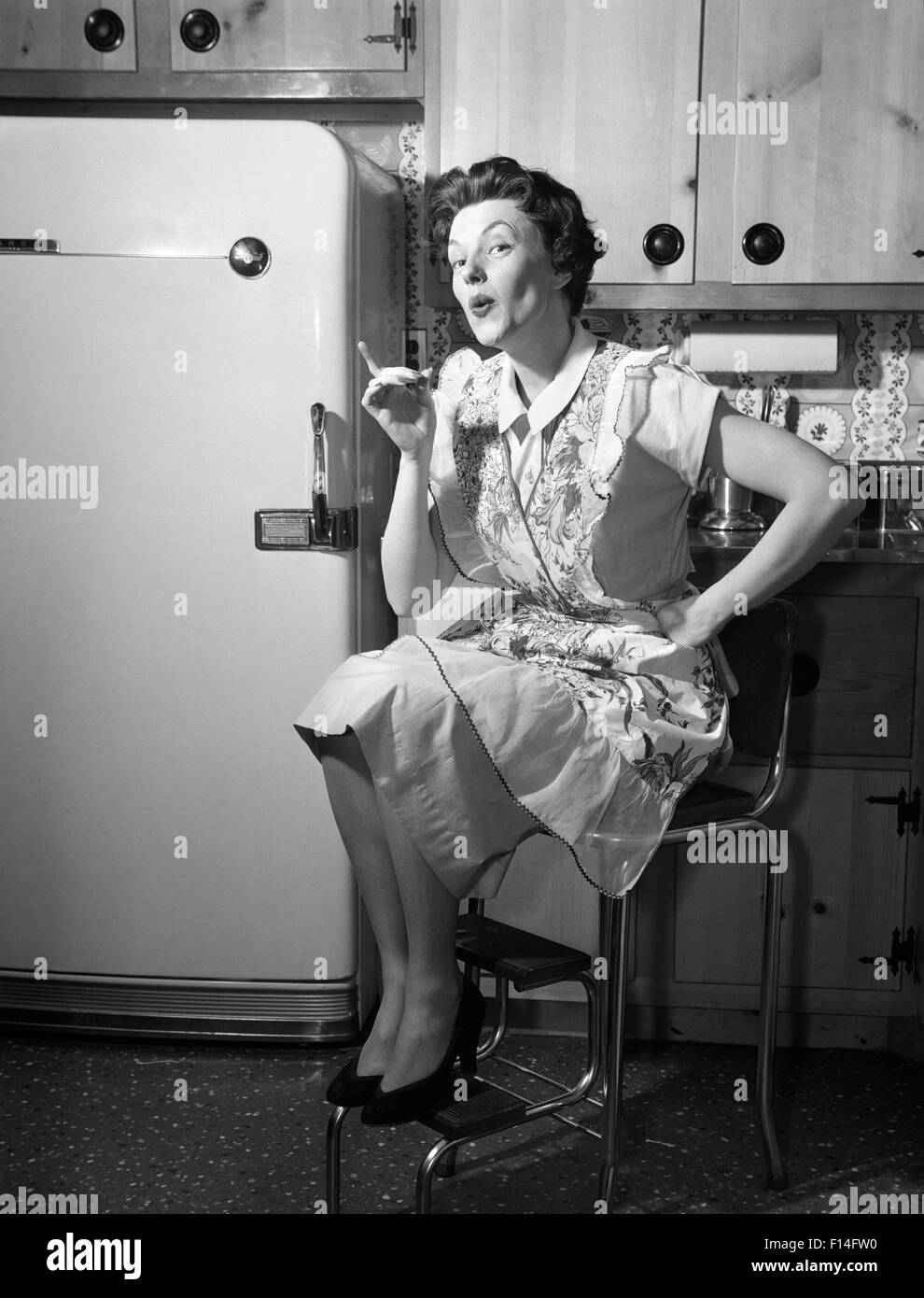 1950s Housewife Sitting On Stool In Kitchen Pointing