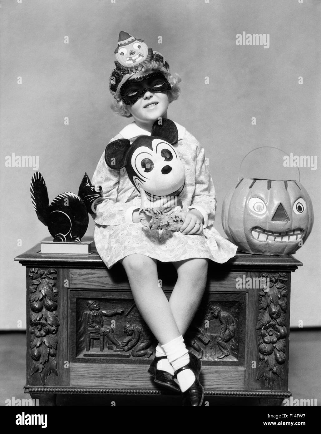 1930s Little Girl Holding Mickey Mouse Toy Wearing Mask
