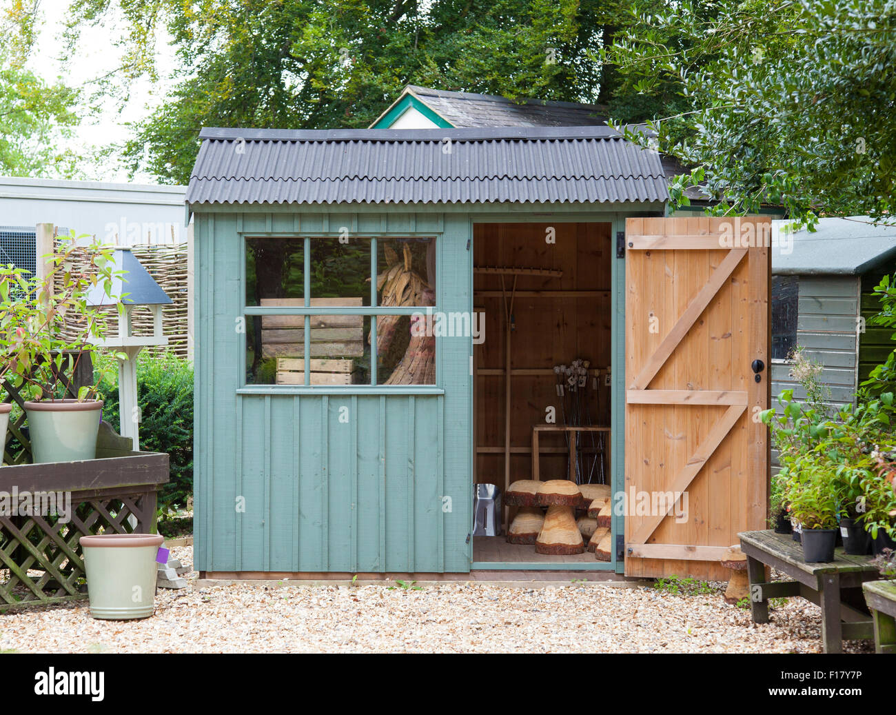 A beautiful garden shed surrounded by pots and plants