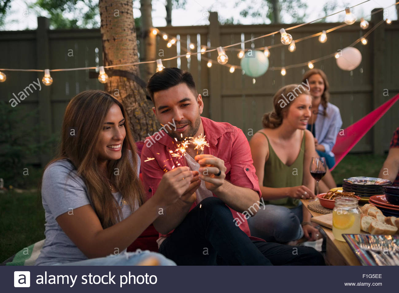 couple lighting sparklers at backyard dinner party stock photo