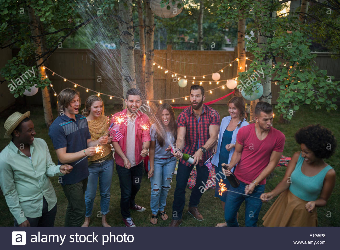 friends with sparklers at backyard party stock photo royalty free